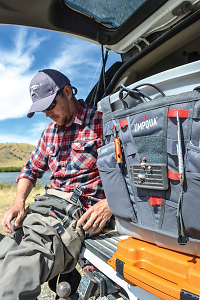 man sitting on tailgate with Umpqua Tailgater organizer