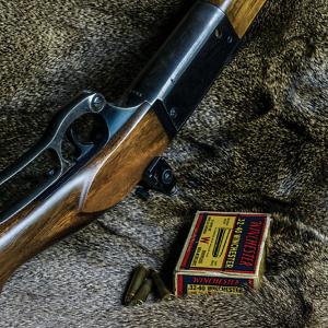 gun and bullet box on fur